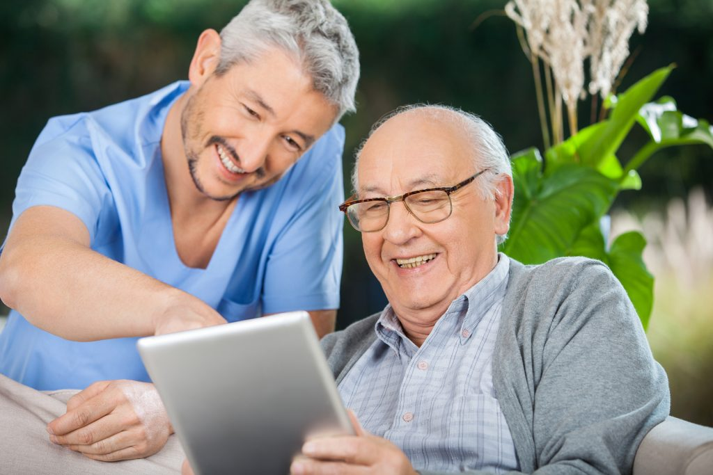 Happy male nurse and senior man enjoying while using tablet computer in nursing home porch