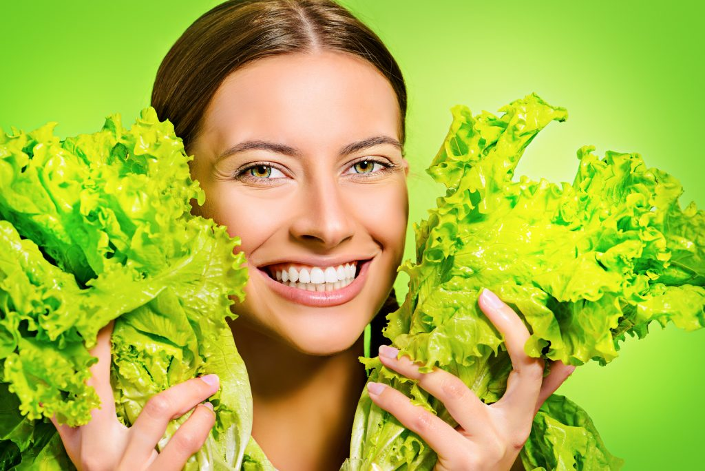 Pretty cheerful young woman posing with fresh green lettuce leav